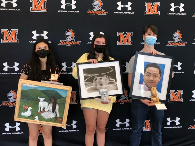 MHS students and winners of the art exhibition Rick Jenkins, Madelyn Baltrotsky, and Selma Depaz are holding their portraits.