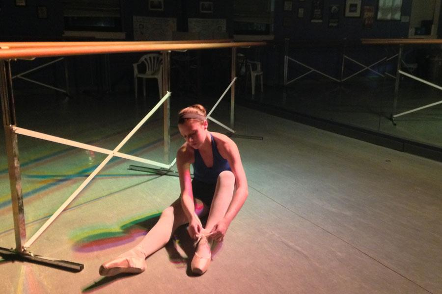 Junior Logan Bramhall ties the last ribbon of her pointe shoe before class. Pointe is one of the most damaging types of dance to a dancers feet.