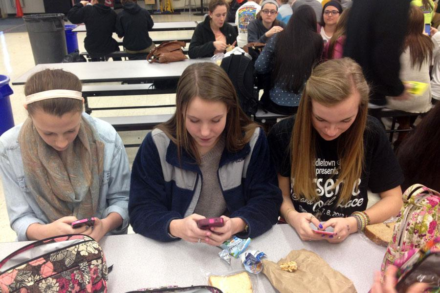 Middletown students Logan Bramhall, Mary Hillsman and Allie Hough catch up on social media and games on their smart phones during their lunch shift.