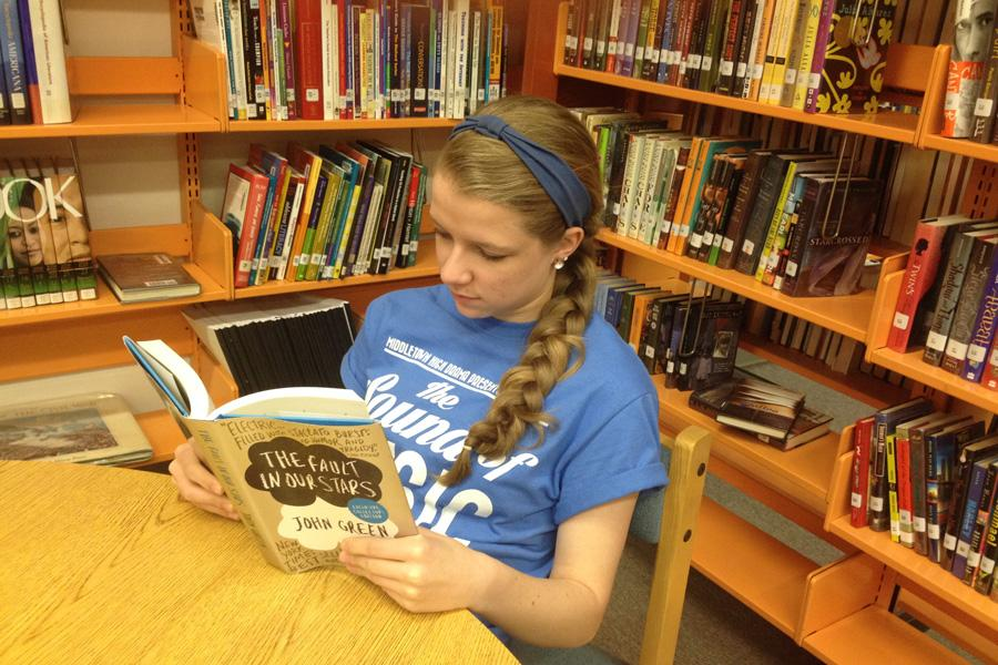 An MHS student sits in the library quietly reading the award winning book The Fault in Our Stars by John Green.