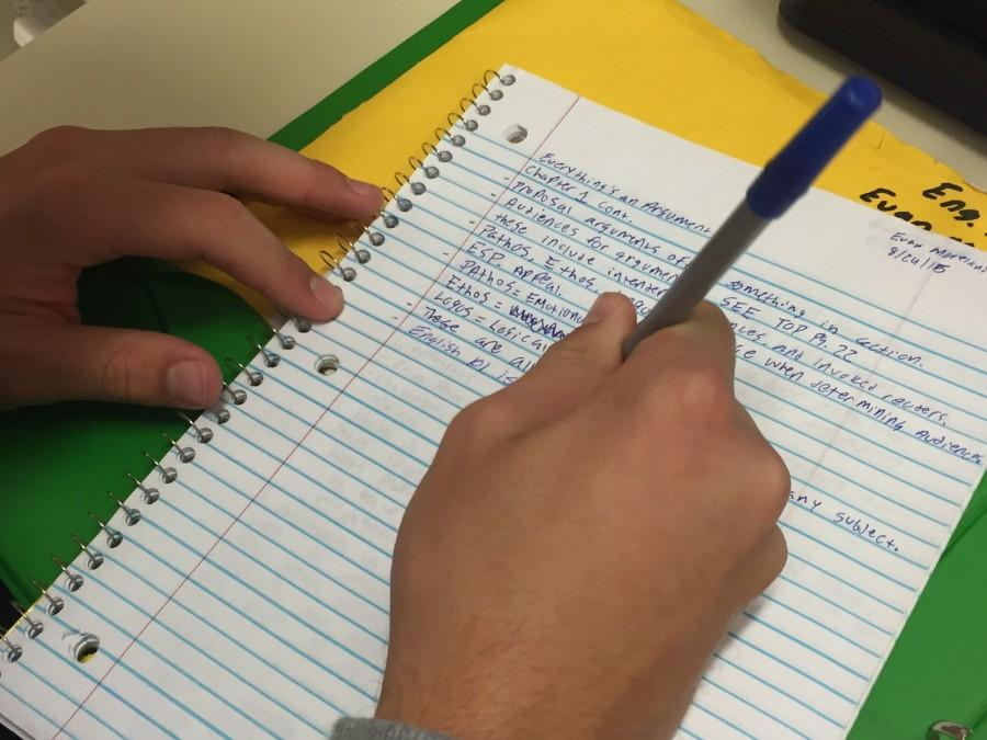 MHS student is taking notes for the new English 101 class. The class requires a similar workload to a college class.