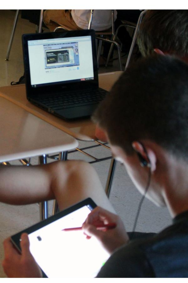 MHS students use their devices in class to work on a project.