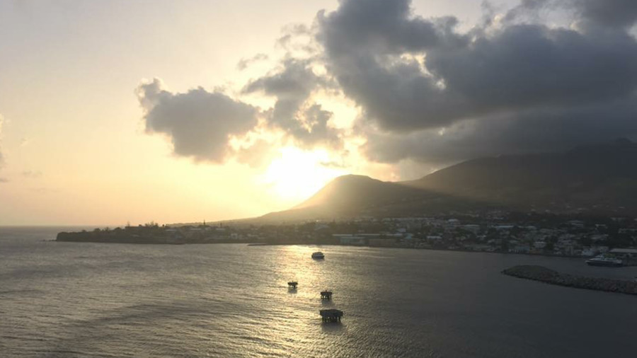The sun is slowly setting on the horizon of one of Saint Kitts' largest mountain