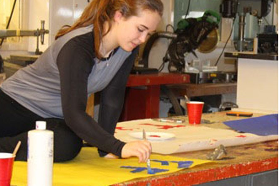FFA member paints spirit day posters.