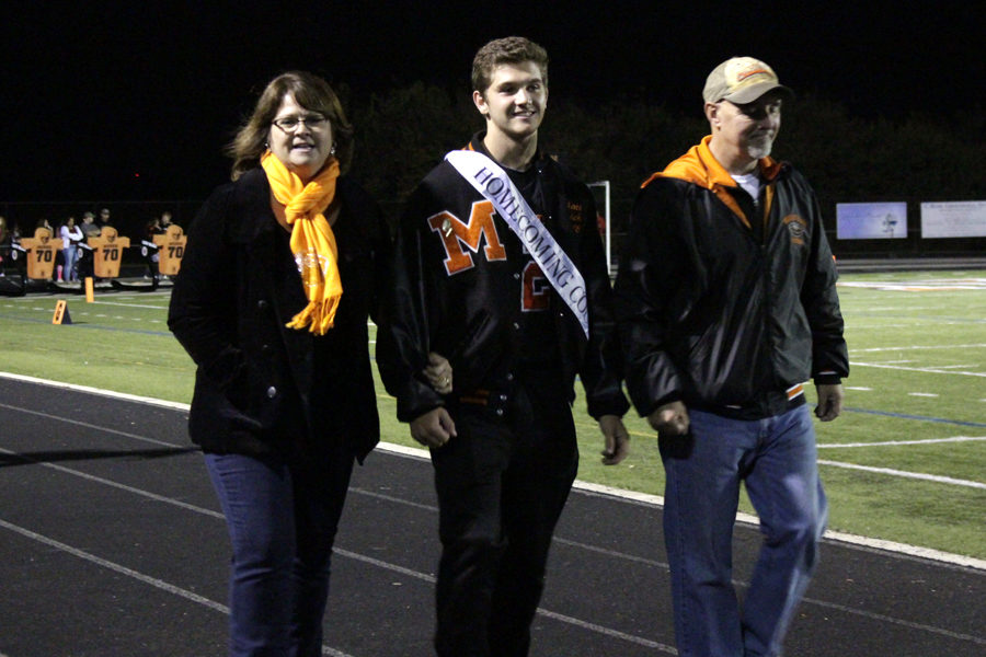 Senior Matt Evich stands with his parents before the homecoming king and queen are announced.