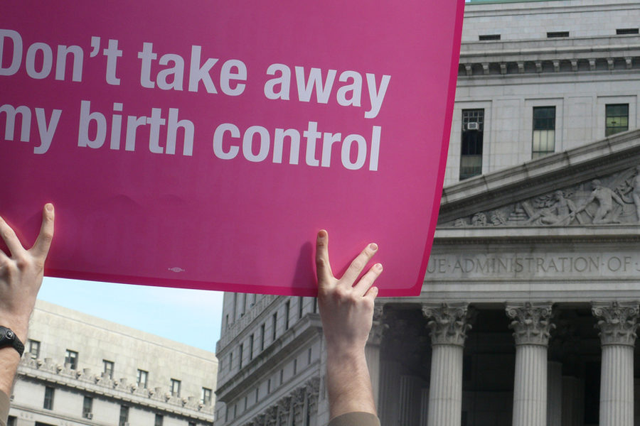 Woman protests the right to birth control in front of the Justice Department. The Trump administration has removed a mandate demanding all employers cover birth control on their provided health insurance plan.