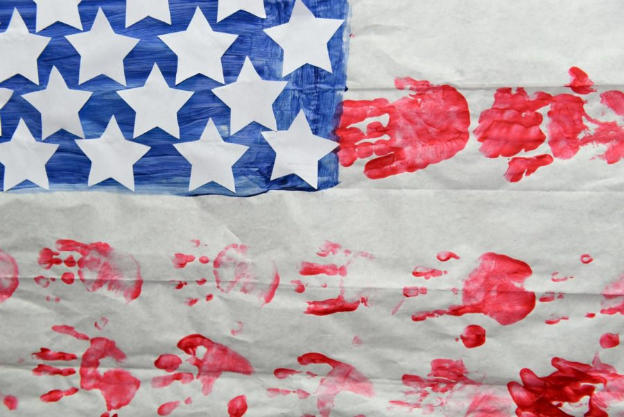 An American flag made of children's hand prints flies high. Memorials such as these mark reverence for the events in Sutherland Springs.
