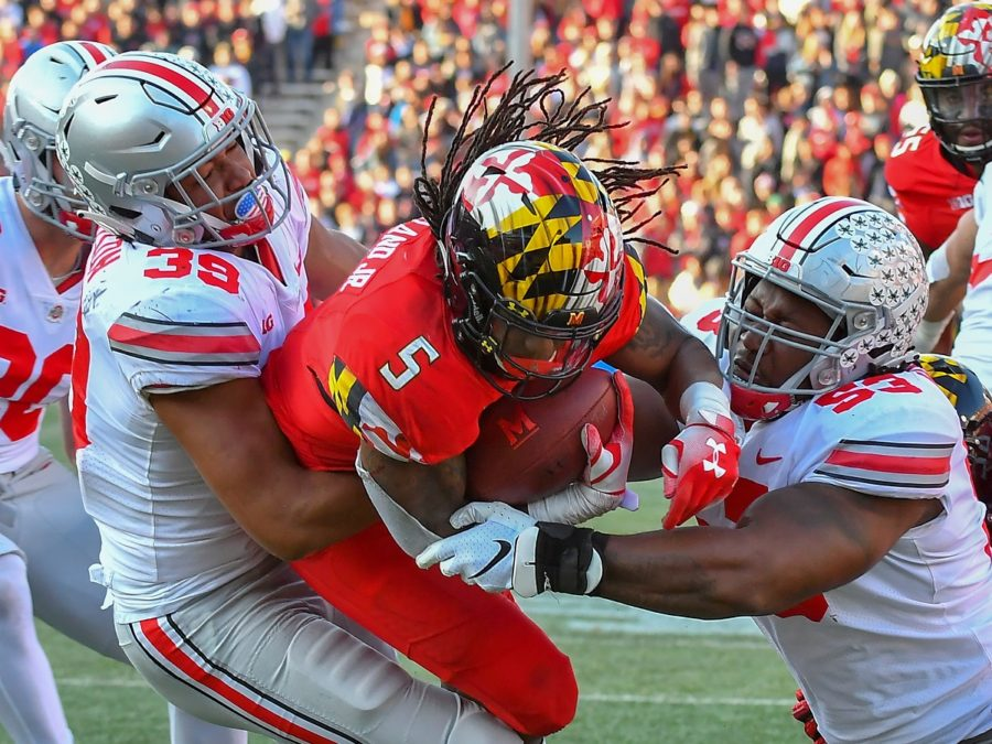 Running back Anthony McFarland of the University of Maryland gets sandwiched between two Ohio State players. UMD vs OSU Football Photo Credit:  David Wolfe