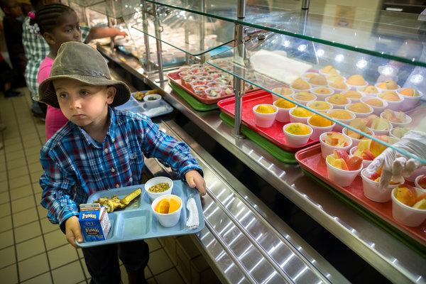 The Trump Administration is cutting back on Obama-era school lunch regulations. Here young student Christopher Parrish collects his lunch.